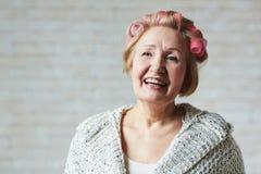 Joyful senior woman with hair curlers stock image