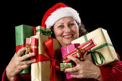 Joyful Senior Woman Hugging Eight Wrapped Gifts. Smiling aged lady with sparkling eyes is embracing eight unicolored wrapped Christmas presents. Santa Claus cap Stock Photos