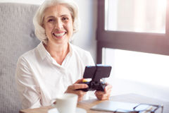 Joyful senior woman resting in the cafe. Express positivity. Cheerful content senior woman smiling and holding game console while sitting at the table Stock Image