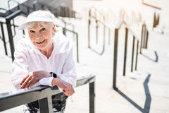 Joyful senior woman resting on huge ladder construction. Waist up portrait of happy old lady standing on top of city stairs outside building. She is leaning on royalty free stock photos