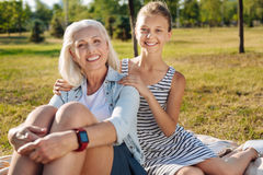 Joyful senior woman sitting in the park with her cute granddaughter. True emotions. Positive delighted smiling senior women sitting in the park with her Stock Photography