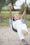 Joyful senior woman on swing active retirement Stock Photography