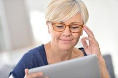 Joyful senior woman using tablet Stock Photo