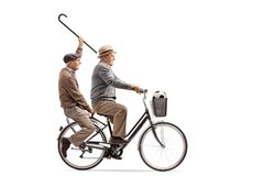 Joyful seniors with a cane and a football riding a bicycle toget Royalty Free Stock Photography