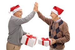 Joyful seniors exchanging christmas gifts and high fiving each o Stock Image