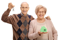 Joyful seniors with pair of keys and model house. Joyful seniors with a pair of keys and a model house isolated on white background Stock Photography