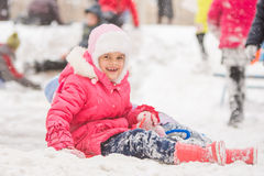 Joyful seven-year child rolled down a hill. Seven year old girl riding winter on a snowy hill surrounded by other children Stock Image