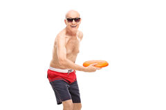 Joyful shirtless senior throwing a flying disc Royalty Free Stock Photography