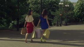 Joyful shopping women walking on city street stock video footage