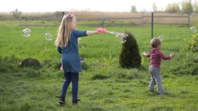 Joyful siblings playing with soap bubbles outdoors stock video