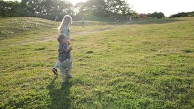 Joyful siblings running through green grassy field. Back view of two playful children holding hands running through green grassy field in park. Young sister and stock video