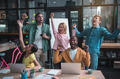 Joyful skilled colleagues are celebrating their triumph Stock Images
