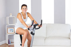Joyful slim woman smiling at camera while training on an exercise bike royalty free stock photography