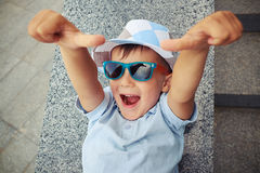 Joyful small boy in sunglasses giving two thumbs up while lying Stock Photo