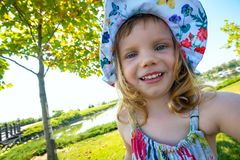 Joyful small girl  taking selfie. During walking in the park on a wonderful sunny day among green trees. Back light Royalty Free Stock Image