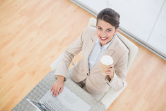 Joyful smart brown haired businesswoman holding a cup of coffee while using a laptop Stock Photo