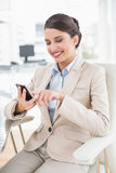 Joyful smart brown haired businesswoman using a mobile phone Royalty Free Stock Image