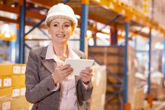 Joyful smart businesswoman holding a tablet. Wholesale market. Joyful smart businesswoman holding a tablet while being in her storehouse Stock Photos