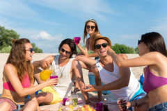 Joyful smiling friends having a picnic. Bright summer. Cheerful smiling friends sitting on the blanket and resting on the beach while having a picnic Stock Photos