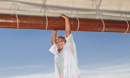 Joyful smiling little girl standing and holding the tall ship beam on beautiful blue sky background Stock Photography