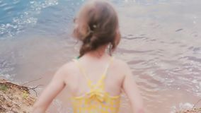 Joyful and smiling little girl in a swim suit jumps into water, splashes it, smiles and has fun. stock video