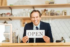 Joyful smiling man standing by the bar and showing plate. My own business. Joyful smiling pleasant man standing by the bar of his shop holding and showing the Stock Photography