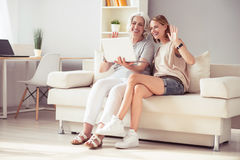 Joyful smiling mother and her adult daughter resting at home Stock Photos