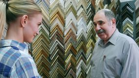 Joyful smiling senior man worker chatting with customer about frames in atelier stock video