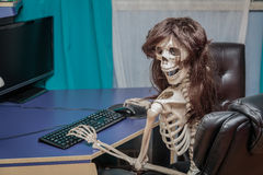 Joyful smiling skeleton in a wig sitting in chair behind the desktop computer Royalty Free Stock Photos