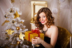 Joyful smiling woman with a gift in her hands Stock Image