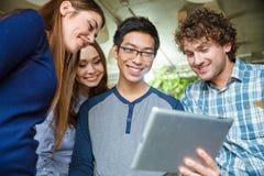 Joyful smiling young friends using tablet Stock Photos