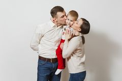 Beautiful European young people on a white background. Emotions, family concept. Joyful smiling young man, women holding, kissing, hugging little cute child boy royalty free stock photos