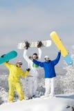 Joyful snowboarders. Portrait of joyful three snowboarders raising their boards Stock Image