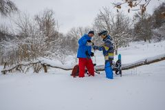 Joyful snowboarders are drinking coffee from thermos in the fore. St after freeride, among snow covered trees and having fun. Cheerful adventure in wilderness Stock Photos