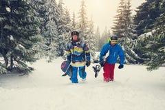 Joyful snowboarders go up the mountain slope. Joyful snowboarders, with snowboards in their hands, go up the mountain slope, amidst huge snow-covered fir trees Stock Photography