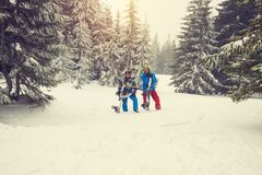 Joyful snowboarders relax amidst huge snow-covered fir trees. Joyful snowboarders, with snowboards in their hands, relax on the mountain slope, amidst huge snow Stock Photo