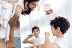 Joyful son cleans teeth, looking in mirror, which keeps father. stock photo