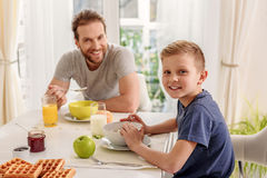 Joyful Son Eating Cereals With His Daddy Stock Images