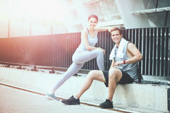 Joyful sporty couple relaxing together after workout. Stock Images