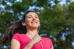 Joyful sporty woman jogging in a park Royalty Free Stock Photography