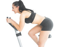 Joyful sporty woman training on an exercise bike Royalty Free Stock Photo
