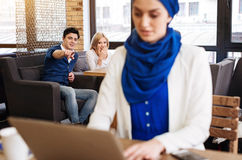 Joyful students humiliating muslim woman. She is odd out. Positive young people sitting in the cafe and pointing at muslim women who is using laptop royalty free stock photo