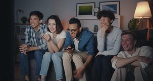 Joyful students watching funny comedy on TV at night laughing having fun. In cozy dark room. Friendship, modern entertainment and youth lifestyle concept stock footage