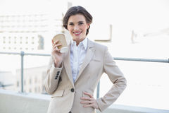 Joyful stylish brown haired businesswoman holding a coffee cup Royalty Free Stock Photos