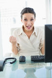 Joyful stylish brunette businesswoman raising her fists Stock Image