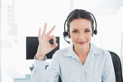 Joyful stylish brunette operator making an okay gesture Stock Images