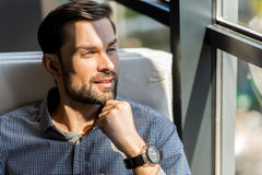 Joyful stylish man enjoying view outside. Follow your dreams. Portrait of cheerful bearded young guy is touching his chin while looking through window with Stock Photo