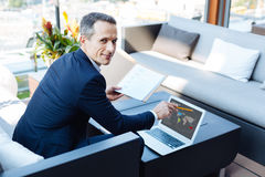Joyful successful entrepreneur looking at you. Business success. Joyful smart successful businessman sitting in his office and looking at you while pointing at Stock Images