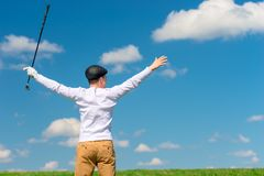 Joyful successful golf course with a golf club. In a green field enjoying the victory Stock Image