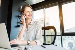 Joyful successful lady enjoying conversation on handset Stock Image